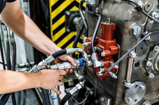 Il lavoratore assembla il trattore o la mietitrebbiatrice in un grande impianto di macchinari. concetto industriale di produzione di macchinari pesanti