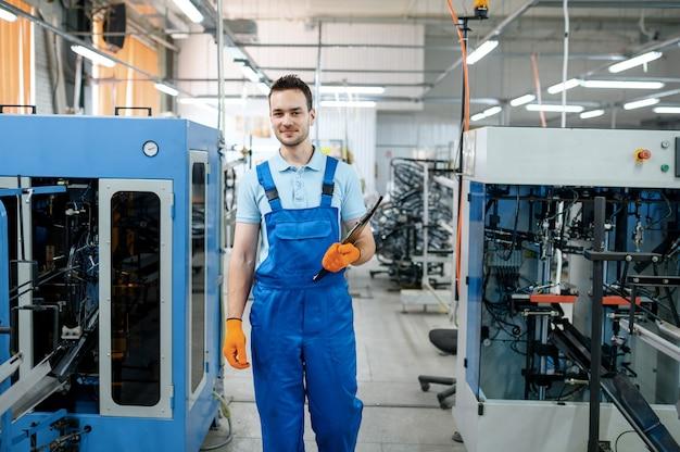 Il lavoratore alla linea di assemblaggio controlla le ruote di bicicletta in fabbrica. produzione di cerchi e raggi bici in officina, installazione parti di biciclette, tecnologia moderna