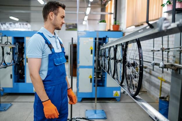 Il lavoratore presso la linea di assemblaggio produce ruote per biciclette in fabbrica. produzione di cerchi e raggi bici in officina, installazione parti di biciclette