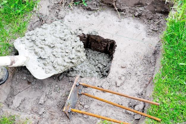 L'uomo del costruttore di operai versa una soluzione di cemento con macerie, liquami, malta cementizia in fossa o foro con pala. preparazione per il processo di costruzione, posa delle fondamenta della casa.