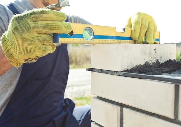 Un operaio costruisce un paletto con i mattoni