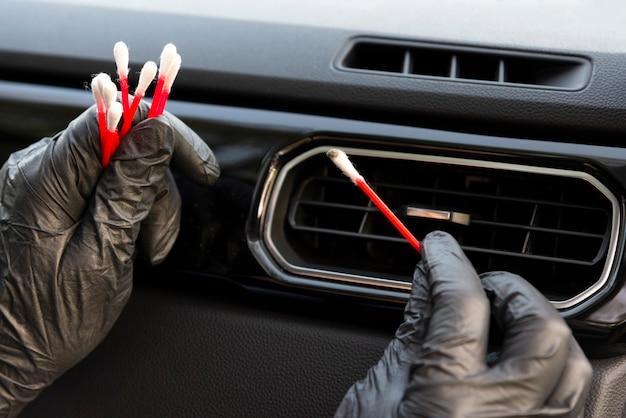 Griglia dello sfiato del condizionatore d'aria dell'automobile di pulizia del lavoratore con la spazzola, primo piano. servizio di lavaggio auto.
