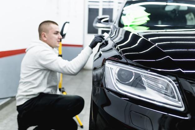 Automobile di pulizia dell'operaio - concetto che dettaglia (o valeting) dell'automobile. messa a fuoco selettiva.