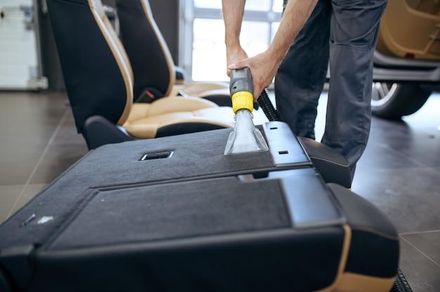 Il lavoratore pulisce i rivestimenti interni dell'auto con l'aspirapolvere, il lavaggio a secco dell'auto e i dettagli.