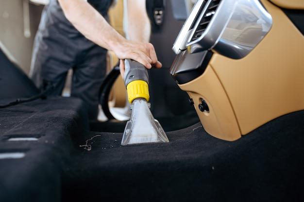 Il lavoratore pulisce l'interno dell'auto con l'aspirapolvere, il lavaggio a secco dell'auto e i dettagli