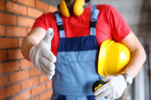 Lavoratore al cantiere che offre la mano in guanti protettivi per agitare il primo piano del cliente