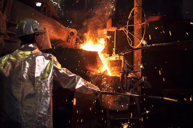 Lavoratore che controlla il processo di metallurgia del ferro fuso, acciaio caldo che versa nell'impianto di produzione.