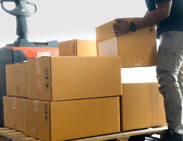 Il corriere del lavoratore sta sollevando la scatola del pacco presso le scatole di spedizione del magazzino