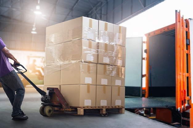 Corriere dell'operaio che scarica la scatola del pacchetto dal contenitore di carico servizio di consegna logistica del magazzino