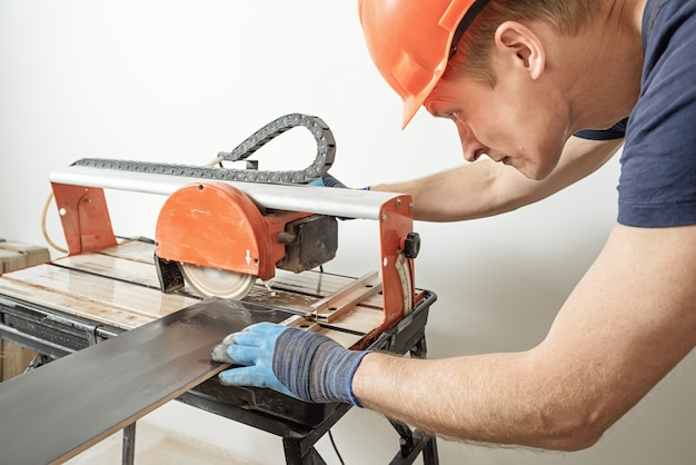 Lavoratore che taglia una piastrella di ceramica su una sega da taglio bagnata