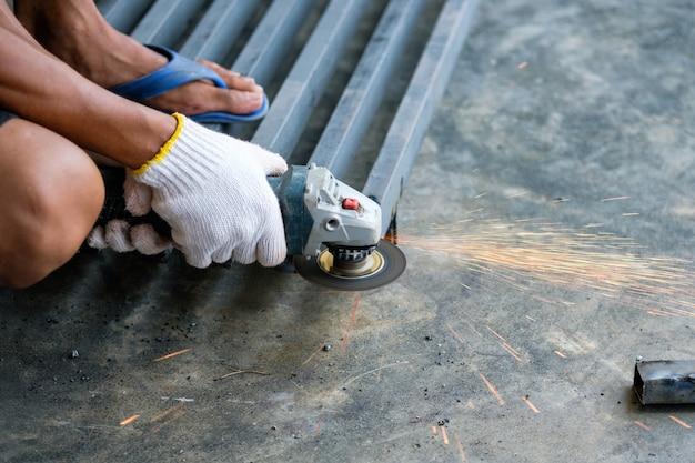 Lavoratore che taglia il metallo con la smerigliatrice e le scintille mentre macina l'acciaio