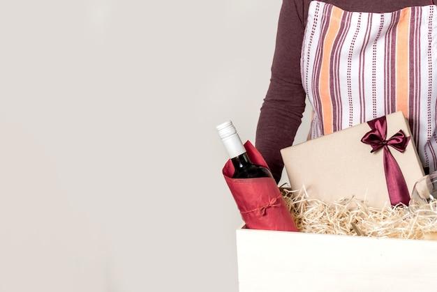 Operaio del servizio di consegna che imballa bottiglia di vino e regali a scatola con paglia per cliente