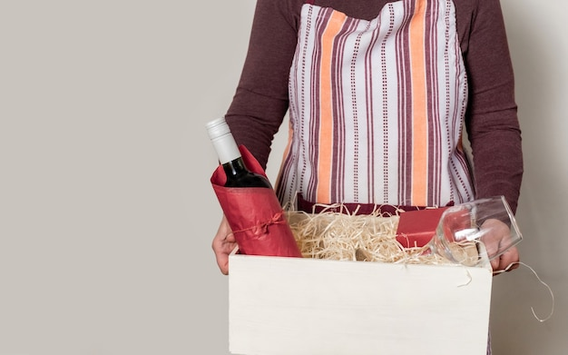 Operaio del servizio di consegna che imballa bottiglia di vino e regali alla scatola con paglia per il cliente.