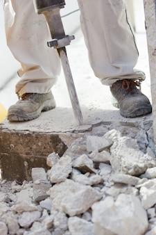 Operaio che demolisce il calcestruzzo con un martello pneumatico