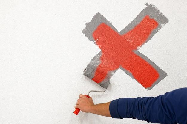 Il lavoratore ha disegnato una croce con un rullo sul muro bianco