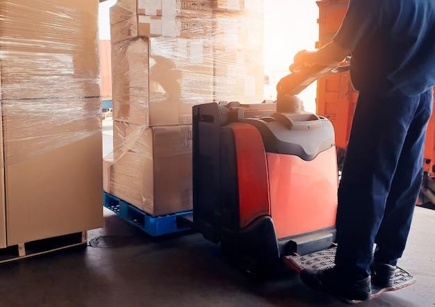 Operaio alla guida del carrello elevatore che carica scatole di pacchi nelle scatole di spedizione del magazzino