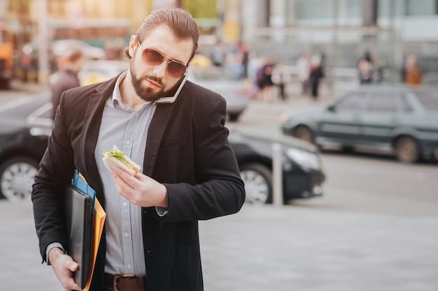 Lavoratore che mangia, beve caffè, parla al telefono, allo stesso tempo. uomo d'affari che fa più compiti. uomo d'affari multitasking.