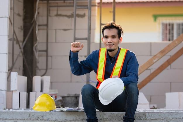 Lavoratore dipendente lavora duramente provato sulla costruzione del sito, ingegnere edile architettura