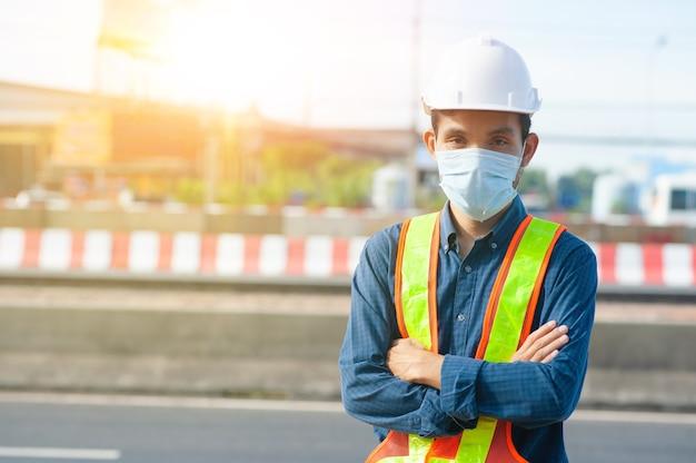 La maschera da indossare dell'ingegnere dell'operaio protegge il coronavirus covid19 che lavora all'aperto sullo sfondo della strada del sito
