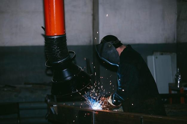 Operaio in fabbrica nel casco è di ferro nel processo di saldatura scintille luminose