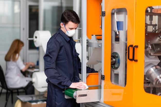 Un lavoratore in una fabbrica per la fabbricazione di maschere mediche