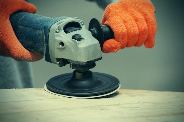 Il lavoratore macina il legno della rettificatrice angolare