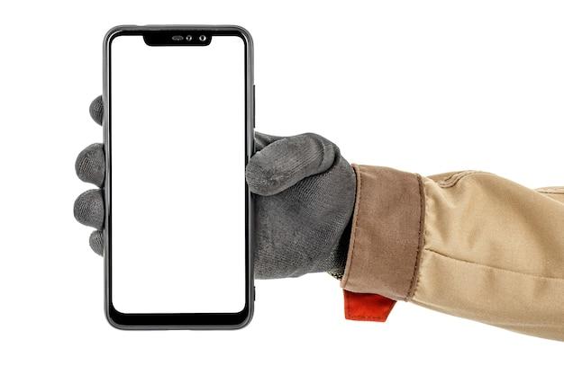 Mano dell'operaio in guanto protettivo nero e uniforme marrone che tiene smartphone moderno con lo spazio della copia sullo schermo su bianco