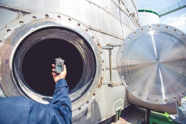 Mano dell'operaio che tiene il rilevatore di gas di ispezione di sicurezza test del gas sul serbatoio inossidabile del tombino anteriore per lavorare all'interno confinato