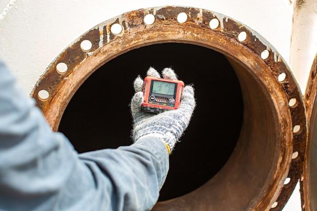 Mano dell'operaio che tiene il rilevatore di gas di ispezione di sicurezza per il test del gas sul serbatoio inossidabile del tombino anteriore per lavorare all'interno confinato