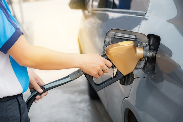 Mano del lavoratore che tiene la benzina dorata della pistola della pompa dell'ugello dalla pompa dell'olio nel serbatoio dell'auto per il rifornimento di carburante.