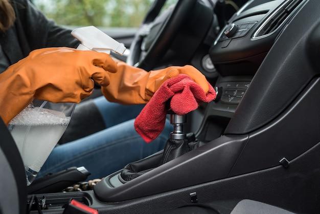 Mano del lavoratore indossa guanti per la pulizia degli interni dell'auto per la prevenzione covid-19