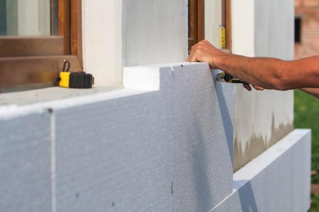 Mano dell'operaio con livello e coltello per misurare e tagliare un foglio di schiuma poliuretanica rigida bianca