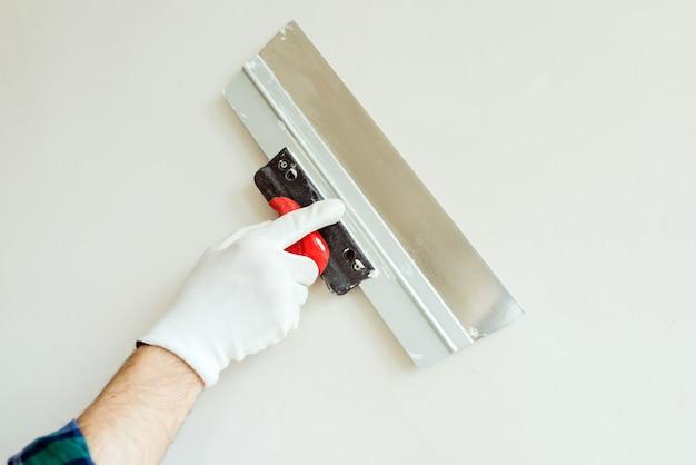 Mano dell'operaio con la spatola sulla parete bianca