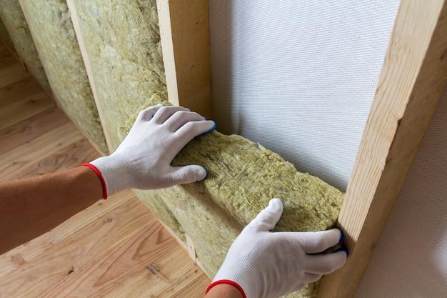 Mani del lavoratore che isolano lana di roccia nel telaio di legno.
