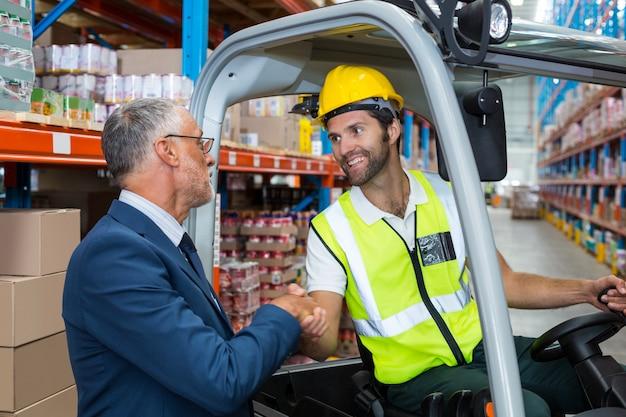 Handshaking del lavoratore con la persona senior ben vestita