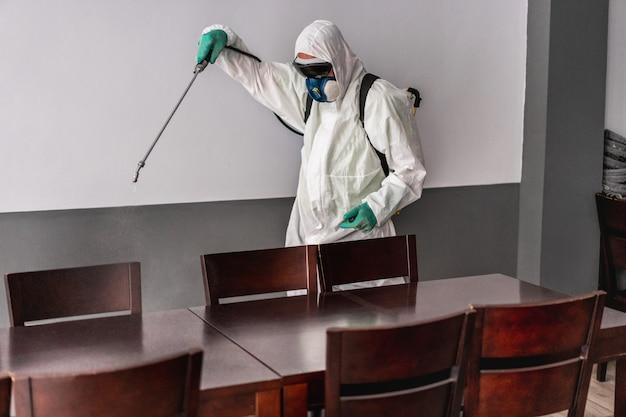 Lavoratore in tuta ignifuga che indossa una maschera protettiva durante la disinfezione all'interno del bar ristorante