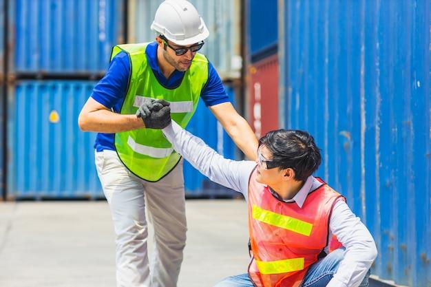 Problema di salute del lavoratore stanco stressante e caduta dal duro lavoro con il supporto di amici nell'area del porto di spedizione merci