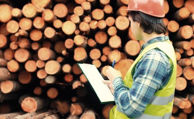 Il lavoratore in casco conta il legname di legno