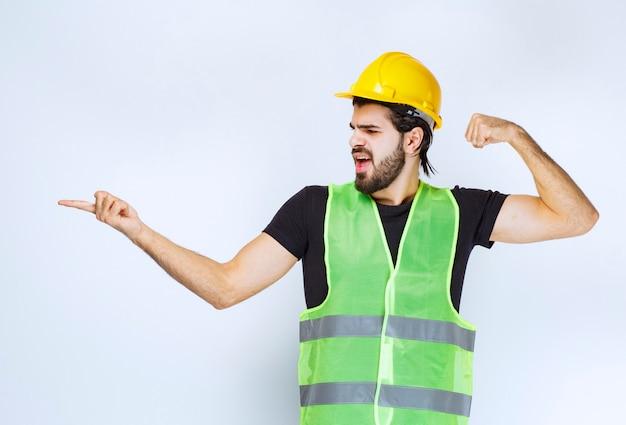 Operaio in casco che indica al lato sinistro e che mostra il suo pugno.