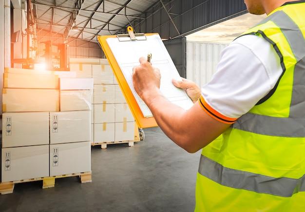 Il lavoratore che tiene gli appunti sta controllando il caricamento della scatola del pacchetto nel trasporto della spedizione del contenitore di carico