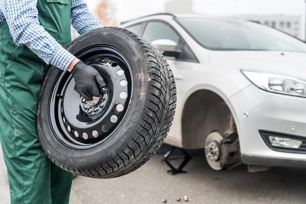 Lavoratore che tiene la ruota di scorta vicino all'automobile rotta