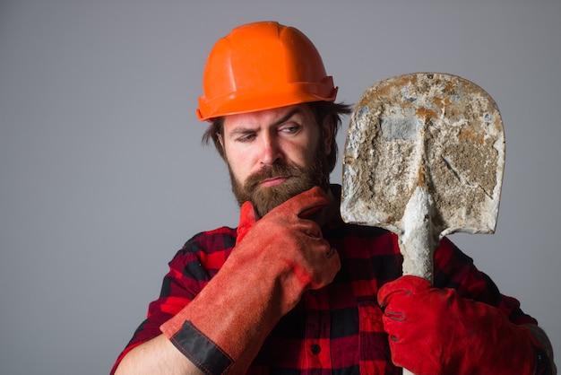 Il lavoratore tiene la vanga. riparazione. operaio con la pala. il costruttore in guanti da lavoro tiene la vanga. costruzione, industria, concetto di tecnologia. builder in elmetto con pala.