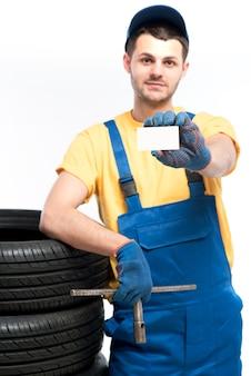 Il lavoratore tiene la gomma e il biglietto da visita vuoto nelle mani