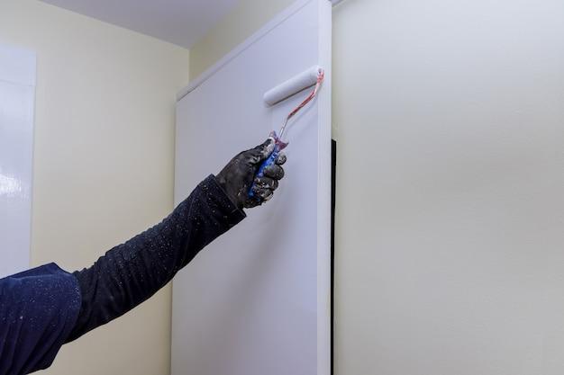 Restauro domestico del lavoratore sulle mani del pittore con i guanti che dipingono la porta usando il rullo a mano