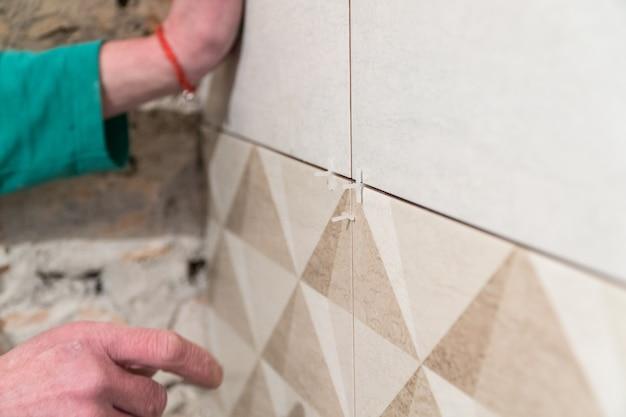 L'operaio inserisce croci di plastica nella cucitura tra le piastrelle la tecnologia di posa delle piastrelle