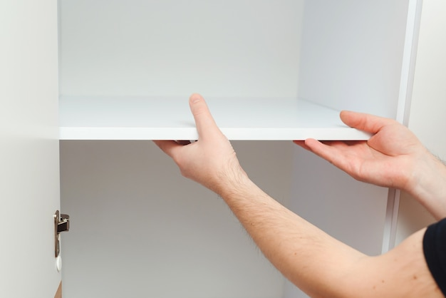 Lavoratore che installa ripiano dell'armadio. concetto di assemblaggio di mobili. riparatore dell'appaltatore che monta nuovi mobili in appartamento moderno