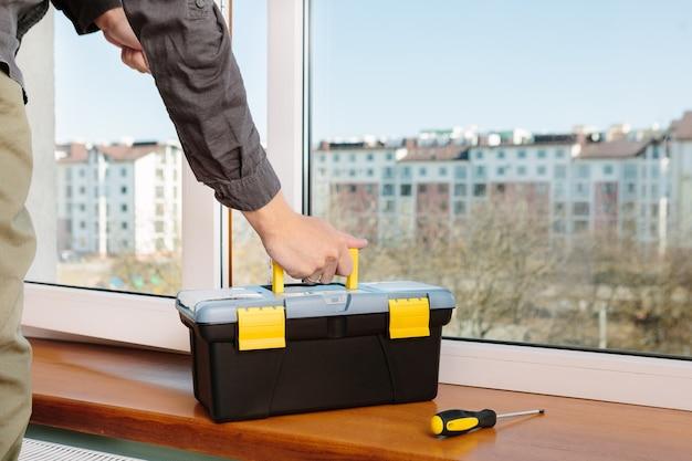 Il lavoratore che installa e controlla la finestra della casa