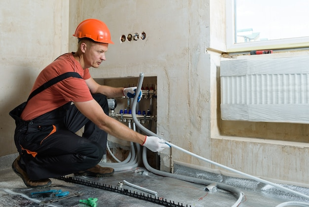 Lavoratore che installa un tubo per il pavimento caldo dell'appartamento