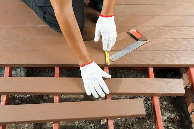 Operaio che installa pavimento in legno per patio
