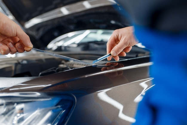 Il lavoratore installa la pellicola protettiva sul cofano dell'auto